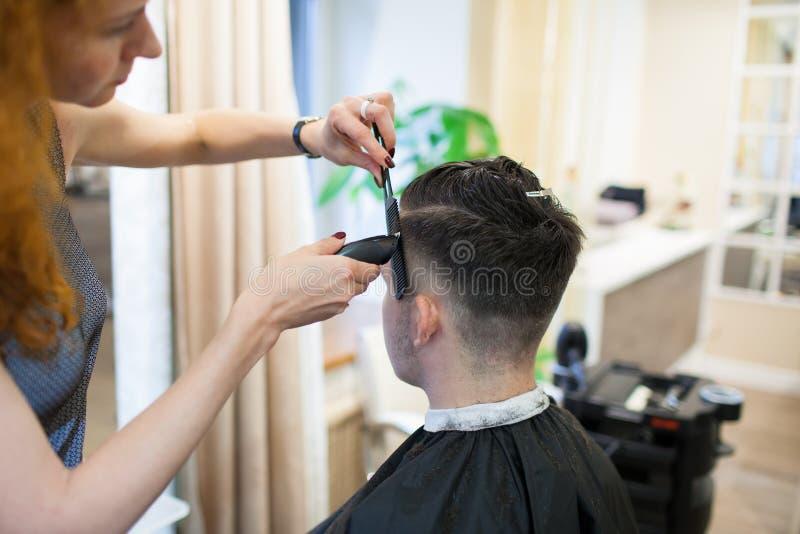 有卷曲红色头发的女孩美发师切开美容院的年轻,英俊的人 免版税图库摄影