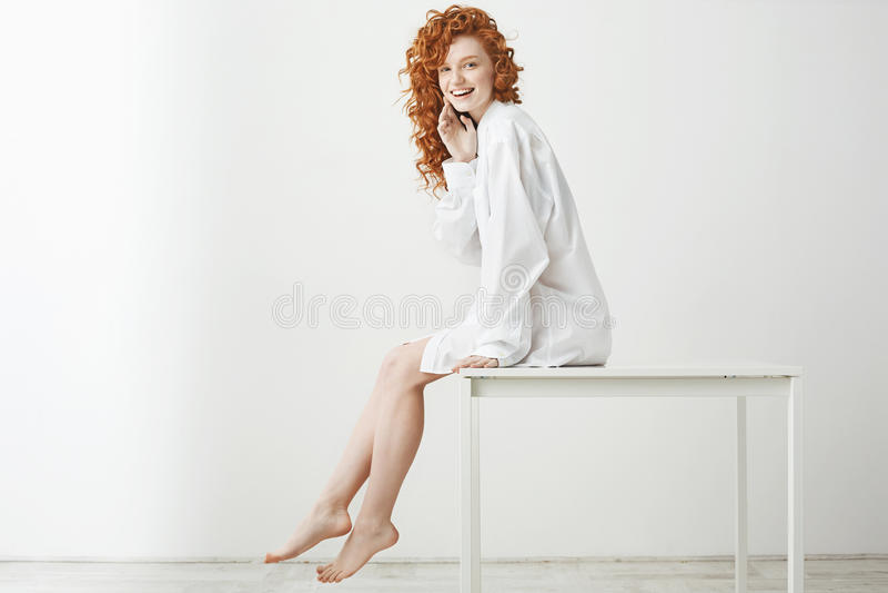 有卷曲红色头发的笑嬉戏的相当嫩的女孩摆在坐在白色背景的桌 复制空间 库存图片