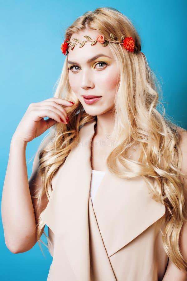 有卷曲金发和一点的年轻人相当白肤金发的女孩降低愉快微笑在蓝天背景,生活方式人 库存图片