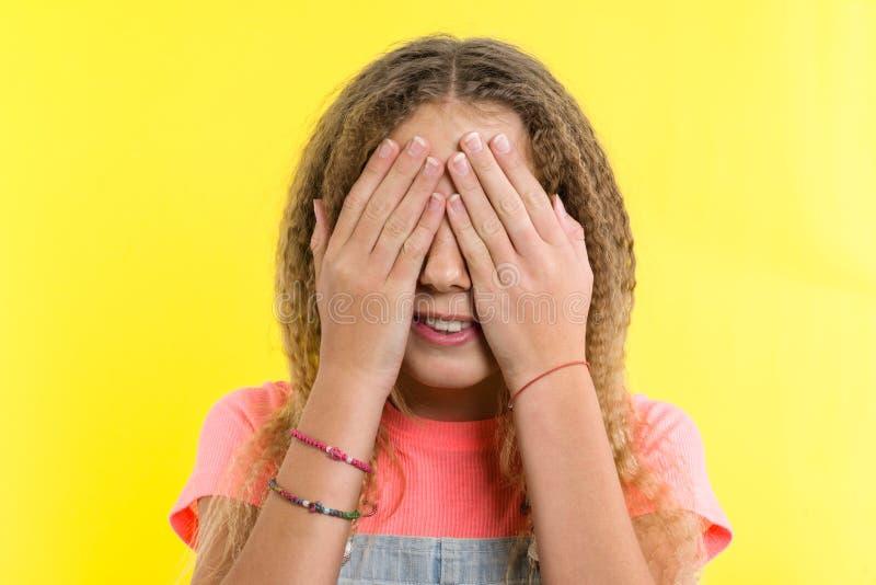 有卷曲金发的十几岁的女孩用手盖了她的面孔,明亮的黄色演播室背景 免版税库存图片