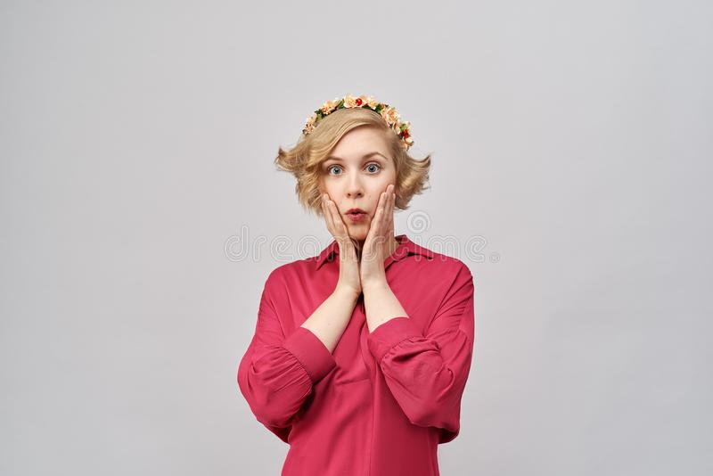 有卷曲金发的美丽的女孩按她的手对她的与一个惊奇吃惊的被迷惑的表示的面颊 免版税库存照片
