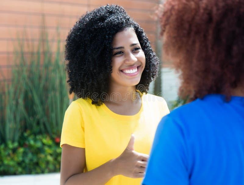有卷曲黑发的笑的拉丁妇女谈话与女朋友 库存照片