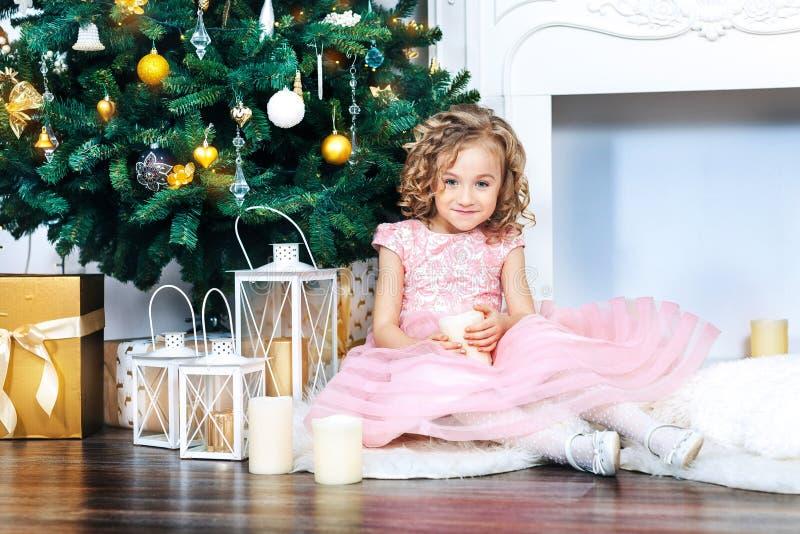 有卷毛的一个甜白肤金发的女孩在一件桃红色礼服在新年装饰坐在白色壁炉和圣诞树得体 免版税图库摄影