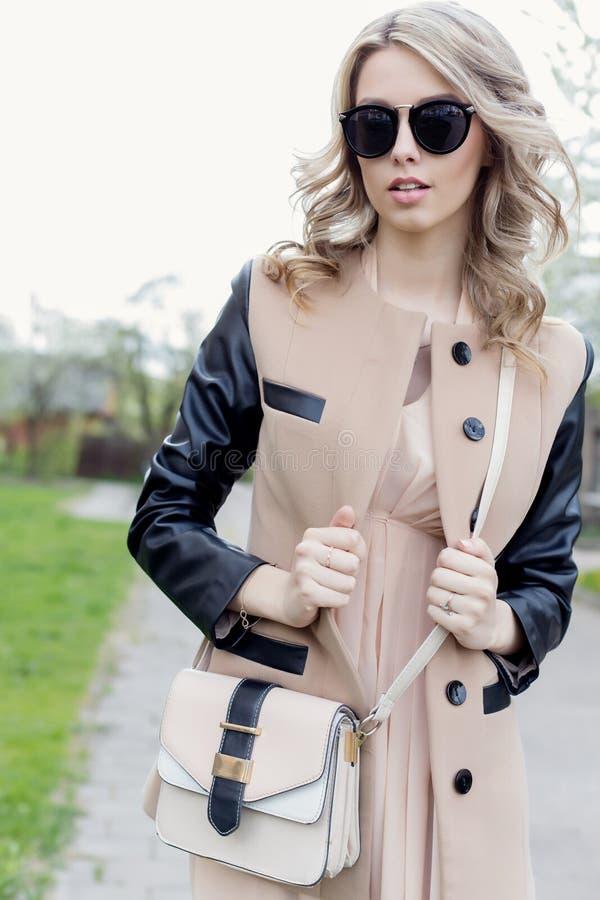有卷毛的美丽的性感的女孩在太阳镜和外套在一春天明亮的天走城市的街道 图库摄影