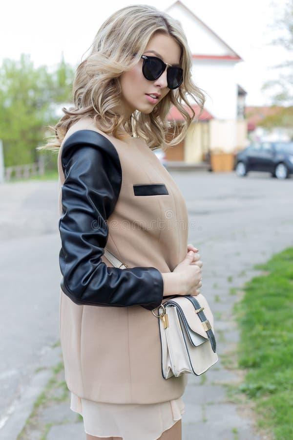 有卷毛的美丽的性感的女孩在太阳镜和外套在一春天明亮的天走城市的街道 免版税库存图片