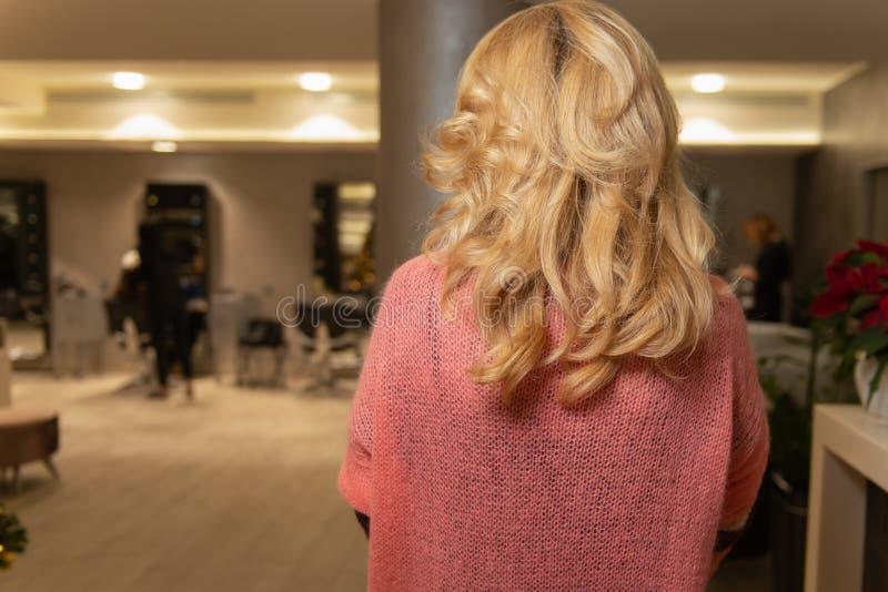 有卷毛的美丽的白肤金发的女孩在豪华发廊 免版税库存图片