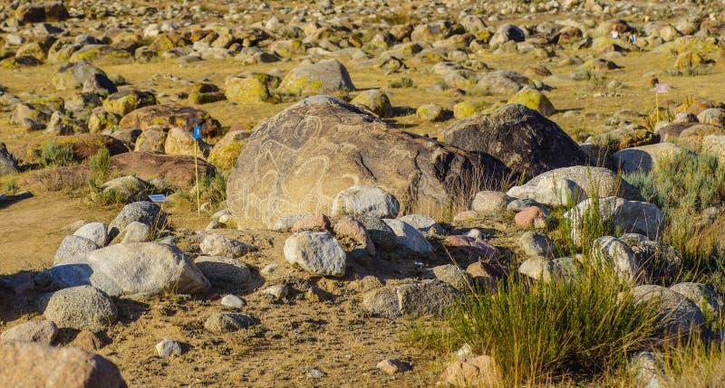 有历史刻在岩石上的文字的古老站点在吉尔吉斯斯坦 免版税库存照片