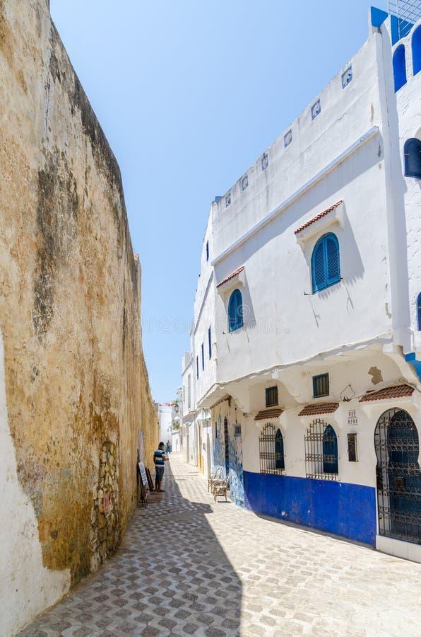 有历史的城市墙壁的石胡同和白色和蓝色在Asilah,摩洛哥,北非洗涤了大厦 免版税库存图片