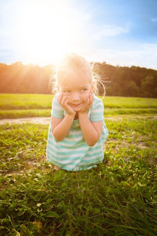 有厚颜无耻的微笑的可爱的白肤金发的小女孩 免版税库存图片