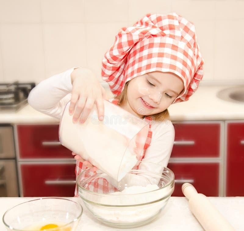 有厨师帽子的微笑的小女孩投入了烘烤的曲奇饼的面粉 免版税库存图片