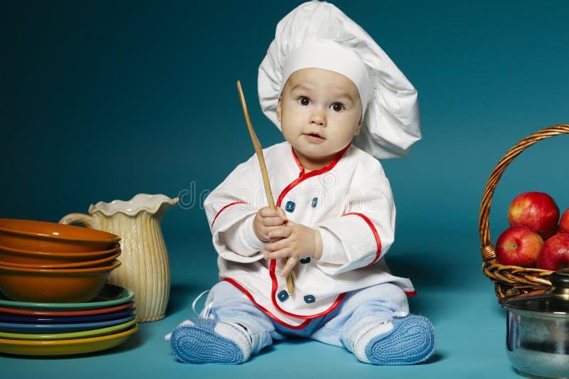 有厨师帽子的逗人喜爱的矮小的婴孩 免版税库存照片