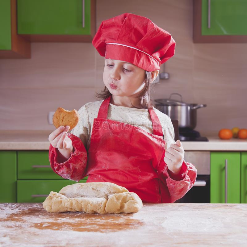 有厨师帽子藏品蛋糕和品尝的它俏丽的小孩女孩 食物,сooking的过程,甜点概念 免版税库存图片