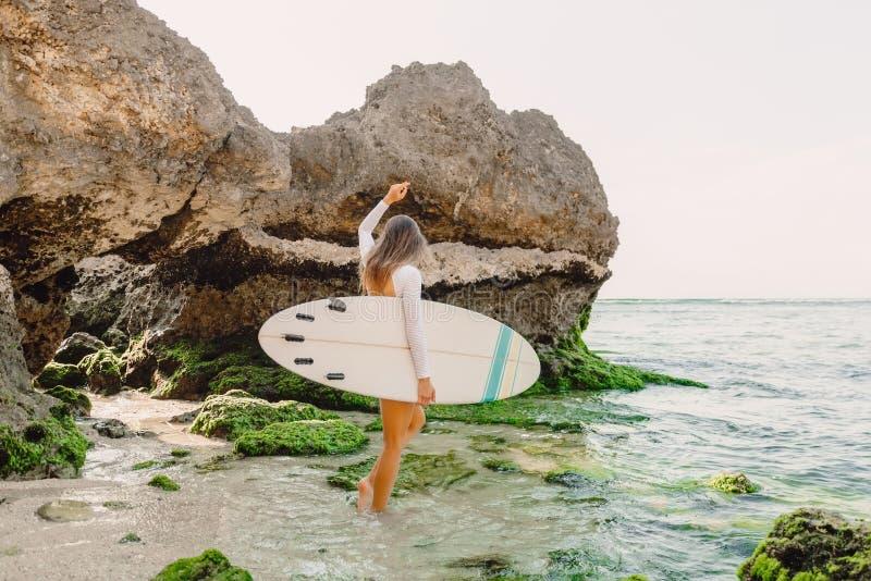 有去冲浪的海洋的冲浪板的可爱的海浪妇女 美丽的运动的妇女 免版税库存照片