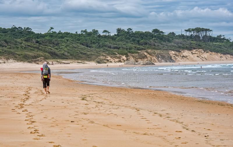 有去在卡米诺de圣地亚哥的海滩的背包的香客 免版税库存图片
