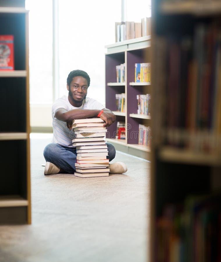 有参加被堆积的书的确信的学生  库存照片
