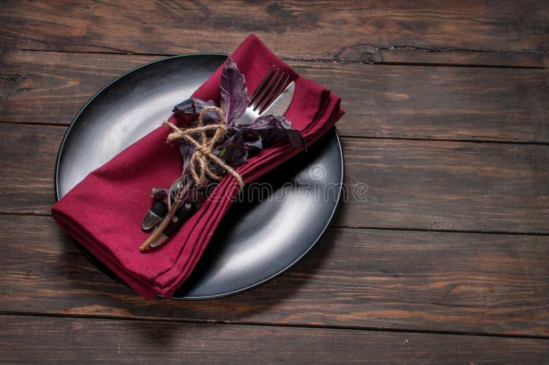有叉子、刀子、餐巾和蓬蒿的黑色的盘子在木桌上 免版税库存图片
