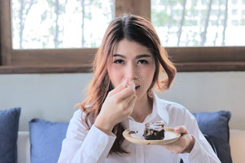 有叉子的吃在咖啡馆的可爱的年轻亚裔妇女画象果仁巧克力蛋糕 免版税库存图片
