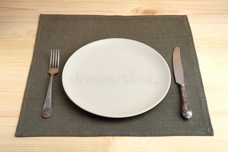 有叉子的空的在餐巾的板材和刀子在桌上 免版税图库摄影