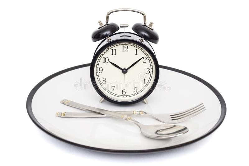 有叉子的黑在板材的闹钟和刀子 查出在白色 吃时间 减重或饮食概念 免版税库存图片