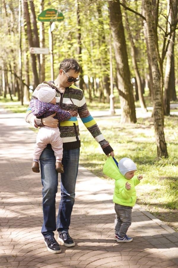 有双摇篮车的年轻父亲走在公园的 库存照片