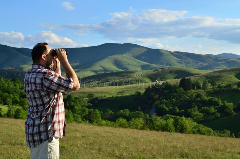 有双筒望远镜的人在夏日 免版税库存图片