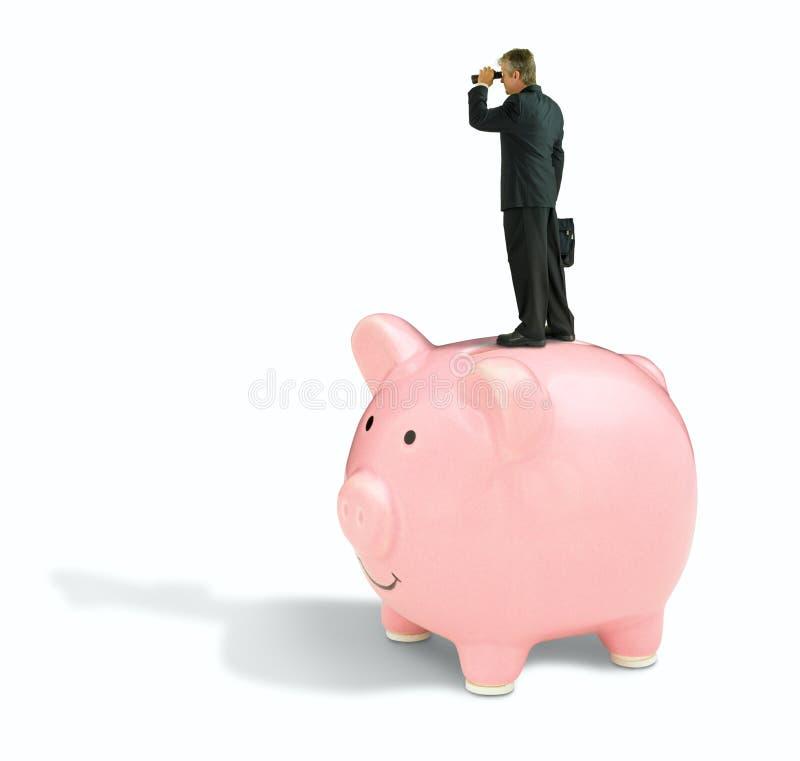 有双筒望远镜的人站立在存钱罐寻找财政成功的隔绝在白色背景 库存图片