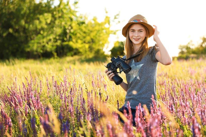 有双筒望远镜的十几岁的女孩在领域 库存图片