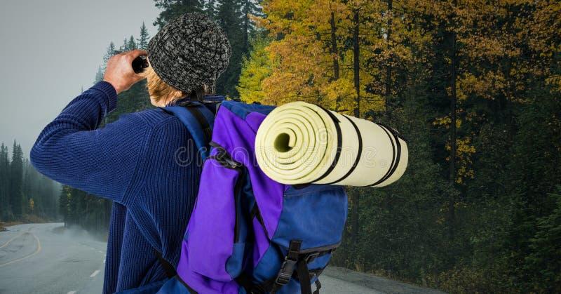 有双筒望远镜的千福年的背包徒步旅行者反对有灰色天空的路 免版税库存照片