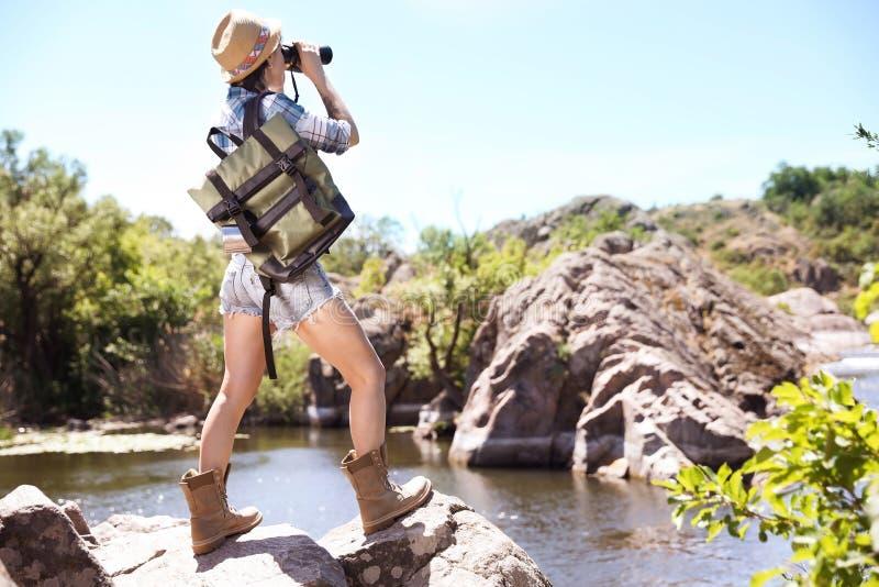 有双筒望远镜的少妇临近河 免版税库存图片