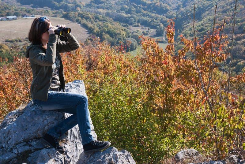 有双筒望远镜的美丽的浅黑肤色的男人观看秋天自然的 免版税库存照片