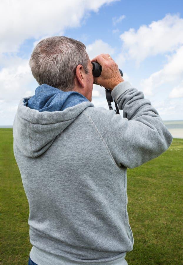 有双筒望远镜的老人 库存照片