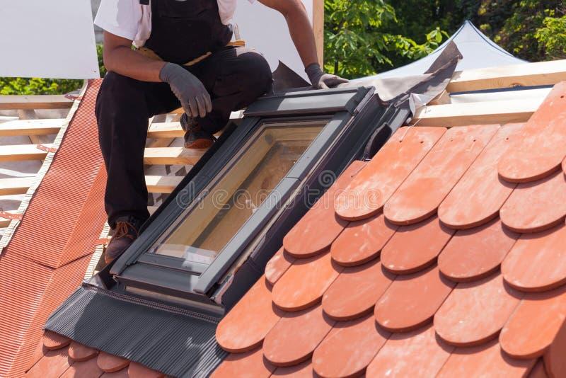 有双重斜坡屋顶的房屋的窗口的设施在红色瓦片一个新的屋顶的  免版税库存图片