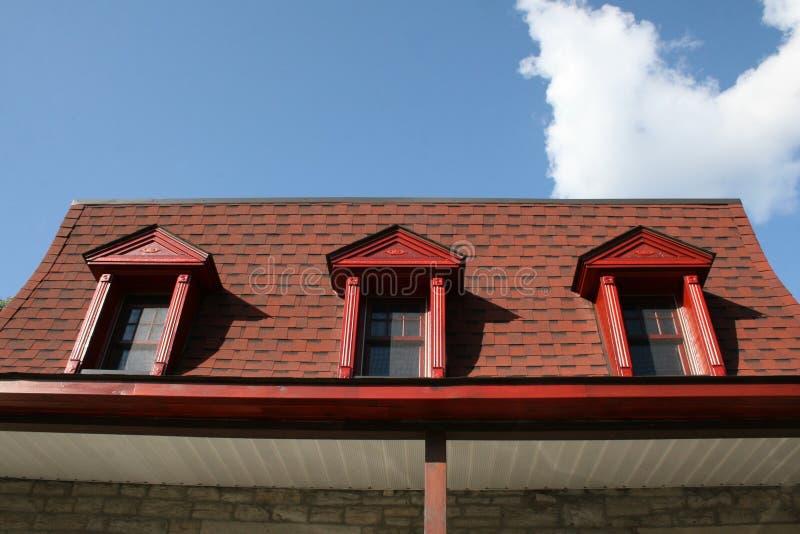 有双重斜坡屋顶的房屋的老红色屋顶 库存照片