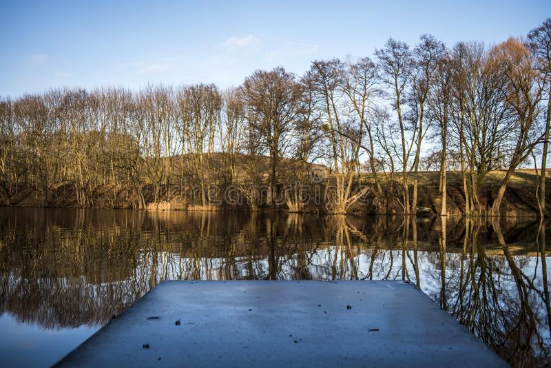 有反射在湖水表面,秋天的树的一座桥梁 图库摄影