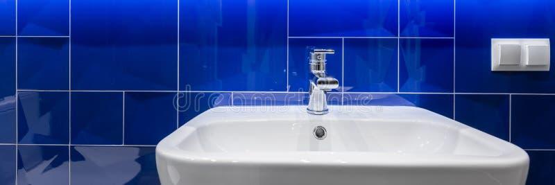 有发光的蓝色瓦片的卫生间 图库摄影