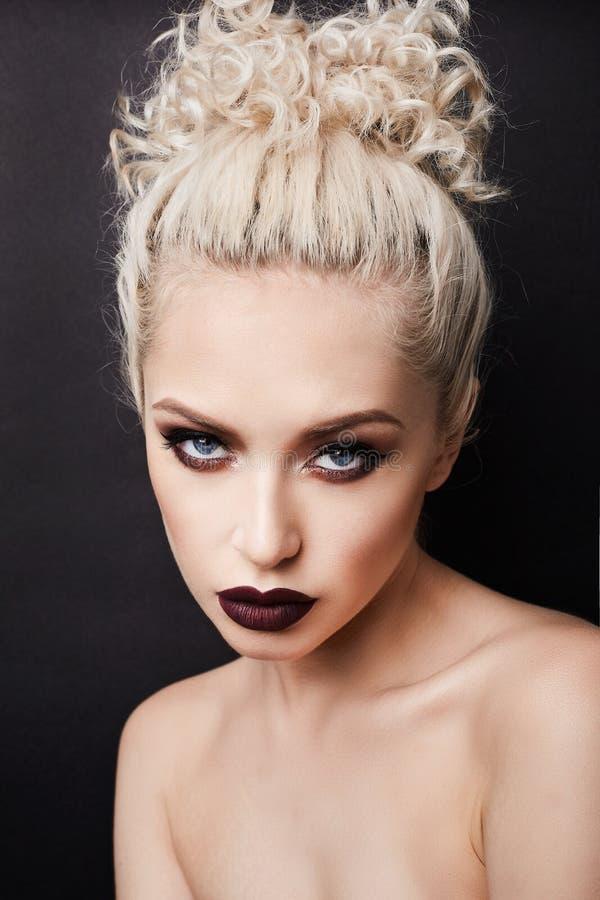 有发烟性眼睛和黑暗嘴唇摆在的性感的女性金发碧眼的女人 库存图片