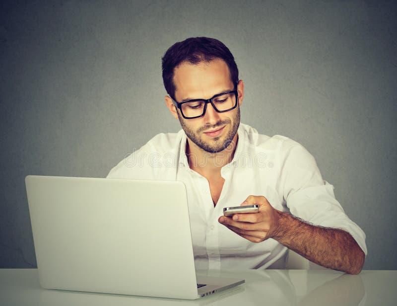 有发短信在手机的膝上型计算机的人坐在桌上 库存图片