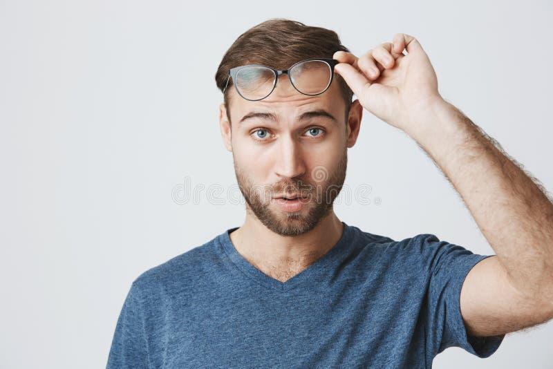 有发茬的困惑的和被迷惑的男学生在蓝色T恤杉穿戴了,看与蓝眼睛的照相机,认为 免版税库存照片