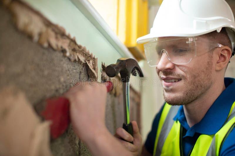 有取消膏药的凿子的建筑工人从墙壁在被更新的议院里 免版税库存照片