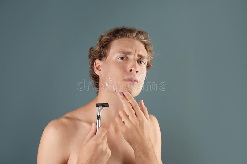 有受伤的面孔的年轻人,当shavin时 免版税库存图片