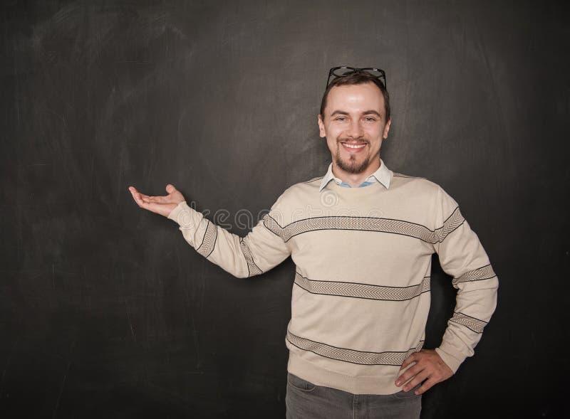 有受欢迎的姿态的微笑的愉快的老师在黑板 图库摄影
