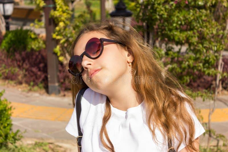 有变冷在公园的sunslasses的俏丽的少女 库存照片