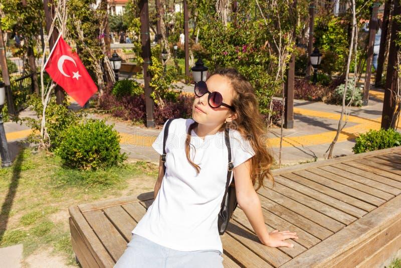 有变冷在有土耳其旗子的公园的sunslasses的俏丽的少女 免版税库存图片