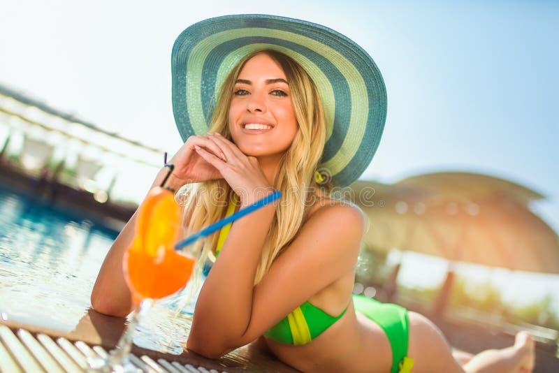有变冷在热带太阳的鸡尾酒杯的妇女在轻便折叠躺椅的游泳池附近 免版税库存照片