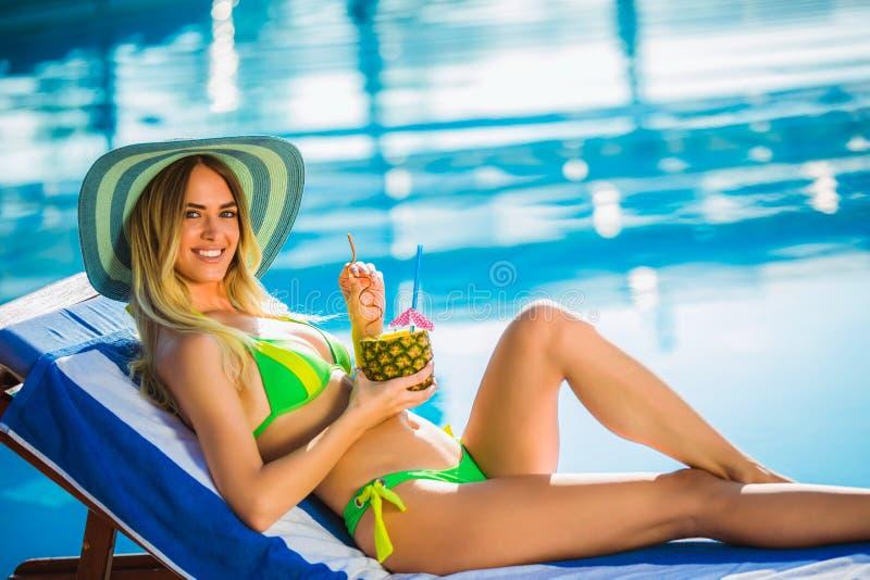 有变冷在轻便折叠躺椅的游泳池附近的鸡尾酒杯的妇女 免版税库存图片
