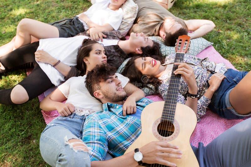 有变冷在野餐毯子的吉他的朋友 免版税库存图片