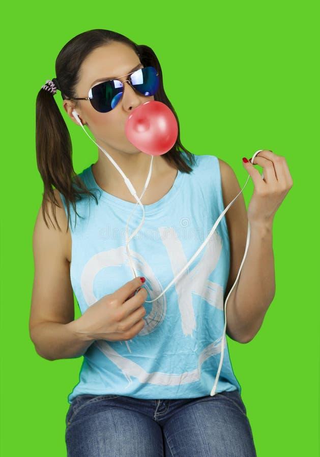 戴有口香糖泡影的美丽的滑稽的女孩太阳镜听到音乐 免版税库存图片