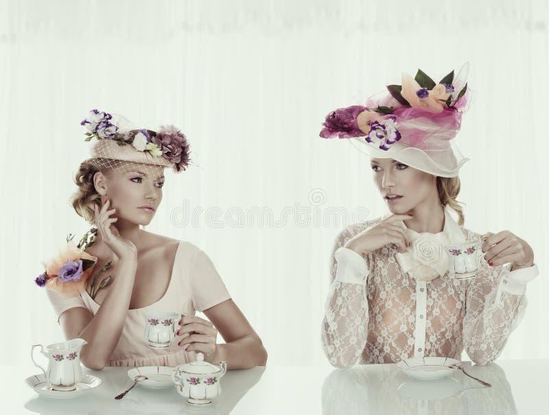 有古典茶具和花帽子的白肤金发的女孩 库存图片