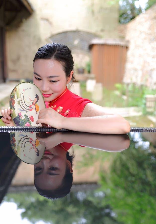 有古典被绣的爱好者的亚裔中国池氏pao cheongsam妇女享受在古镇被倒置的反射的轻松的业余时间 免版税库存照片
