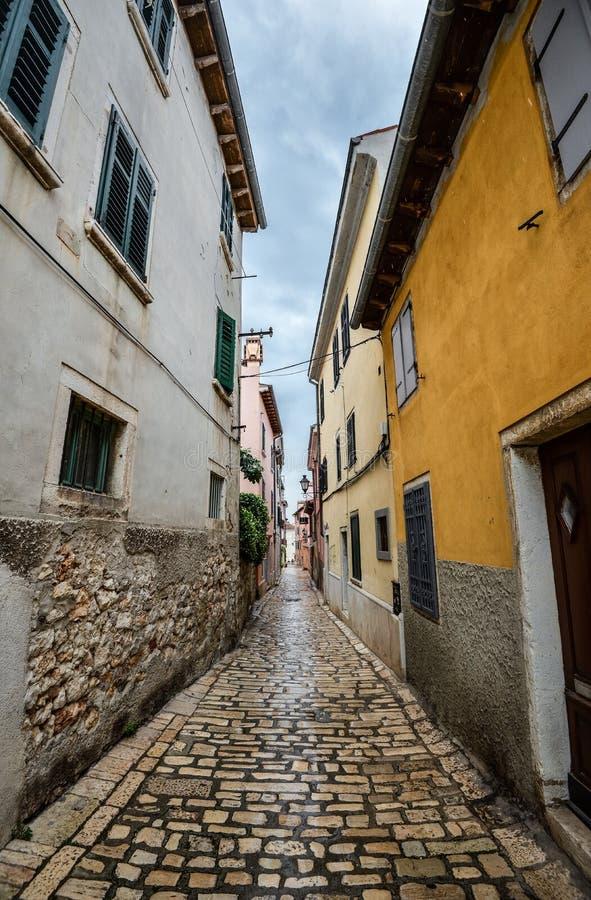 有古老修造的门面和铺路石的美丽的狭窄的街道在沿海城镇罗维尼,克罗地亚 免版税库存图片